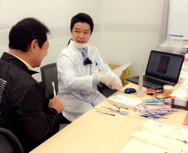 お坊さんは歯医者さん!? 健康診断でお口のなかをカメラで映して説明する大島さん